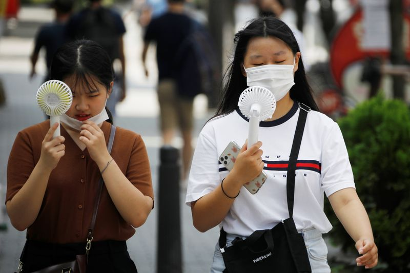 © Reuters. Las mujeres que usan máscaras para prevenir la propagación de la enfermedad por coronavirus (COVID-19) usan ventiladores portátiles para refrescarse en Seúl.