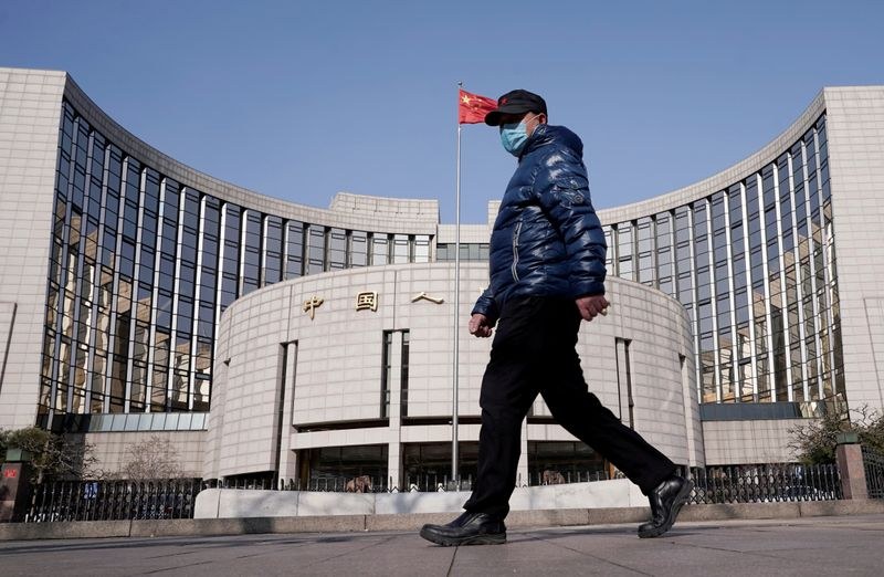 © Reuters. FILE PHOTO: Man wearing a mask walks past the headquarters of the People's Bank of China, the central bank, in Beijing