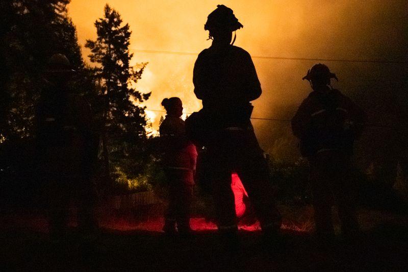 © Reuters. Los bomberos de Santa Rosa monitorean el incendio del complejo de rayos LNU desde una colina vecina en Healdsburg, California