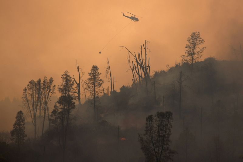 © Reuters. FOTO DE ARCHIVO: FOTO DE ARCHIVO: Helicóptero libera agua cuando el incendio del Complejo Relámpago LNU se desconecta cerca de Middletown, California