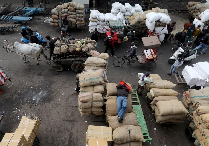 © Reuters. A labourer sleeps on sacks as traffic moves past him in a wholesale market in the old quarters of Delhi