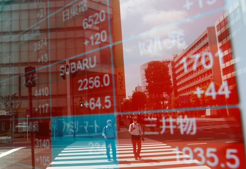 © Reuters. People wearing protective masks, following the coronavirus disease (COVID-19) outbreak, are reflected on a screen showing stock prices outside a brokerage in Tokyo