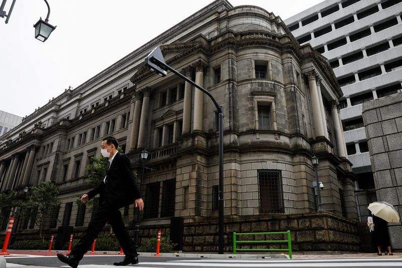 � Reuters. A man wearing a protective mask walks past the headquarters of Bank of Japan amid the coronavirus disease (COVID-19) outbreak in Tokyo
