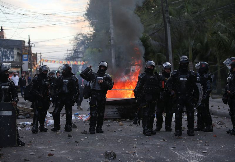 © Reuters. Riot police stand next to a burning garbage container during clashes with protesters after a man, who was detained for violating social distancing rules, died from being repeatedly shocked with a stun gun by officers, according to authorities, in Bogota