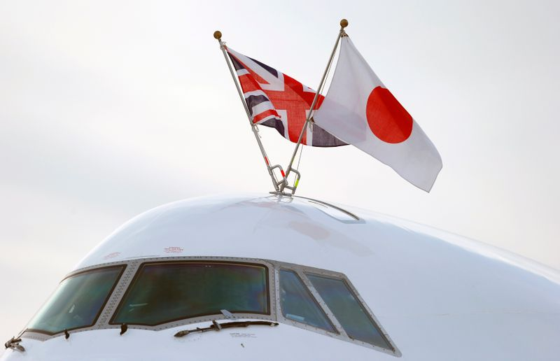 © Reuters. Flags of Japan and the United Kingdom are seen on the aircraft carrying Japan's Prime Minister Shinzo Abe as he arrives to attend the Enniskillen G8 summit, at Belfast International Airport