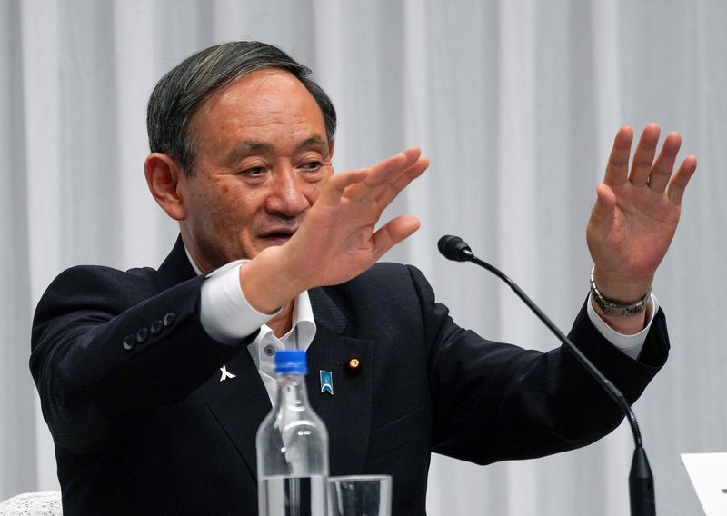 © Reuters. FILE PHOTO: Japan's Chief Cabinet Secretary Yoshihide Suga waves after a debate for the ruling Liberal Democratic Party's leadership election