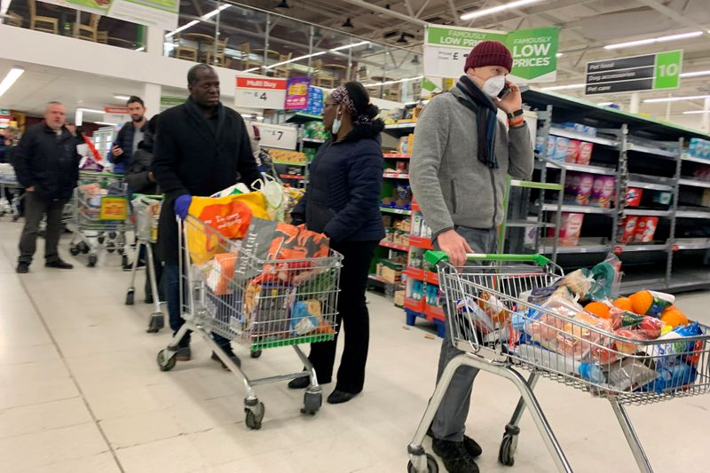 � Reuters. FILE PHOTO: Shoppers queue at a supermarket in London