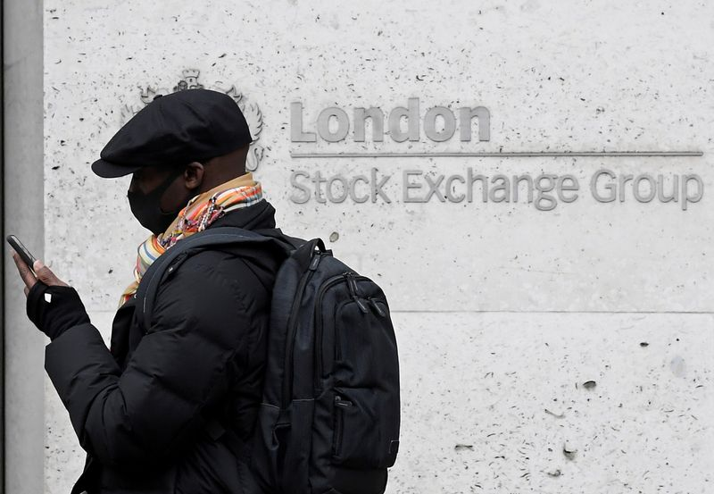 © Reuters. FILE PHOTO: A man wearing a protective face mask walks past the London Stock Exchange Group building in the City of London financial district, whilst British stocks tumble as investors fear that the coronavirus outbreak could stall the global economy, in L