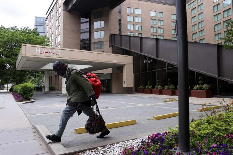 � Reuters. A member of the homeless community walks past a Hyatt hotel that is completely closed to guests during the coronavirus disease (COVID-19) outbreak, in Washington