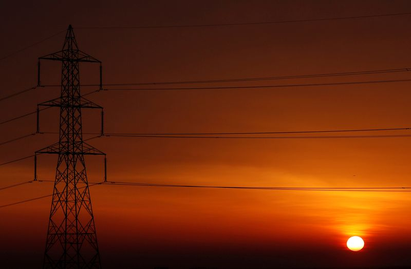 � Reuters. FILE PHOTO: The sun is seen behind high-voltage power lines and electricity pylons at a highway northeast of Cairo