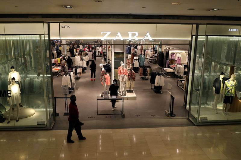 � Reuters. FILE PHOTO: Staff wearing protective mask waits for customers at the entrance of a Zara store, amid the coronavirus disease (COVID-19) outbreak in Kuala Lumpur