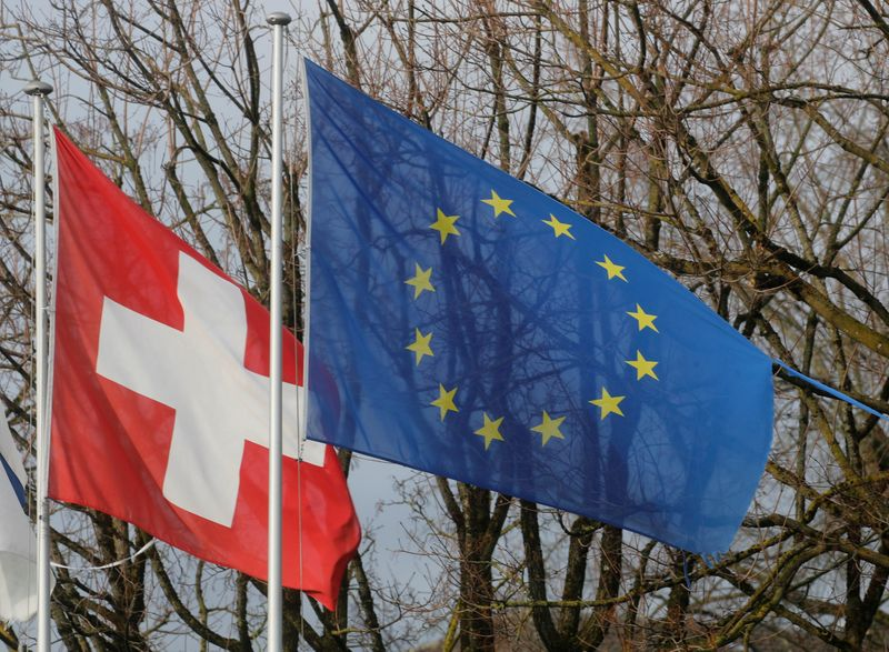 © Reuters. FILE PHOTO: Switzerland's national flag flies beside the one of the European Union in Steinhausen