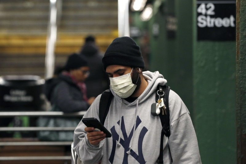 © Reuters. A man wearing a face mask uses his phone in the Times Square subway station, as people react to coronavirus disease (COVID-19) in New York