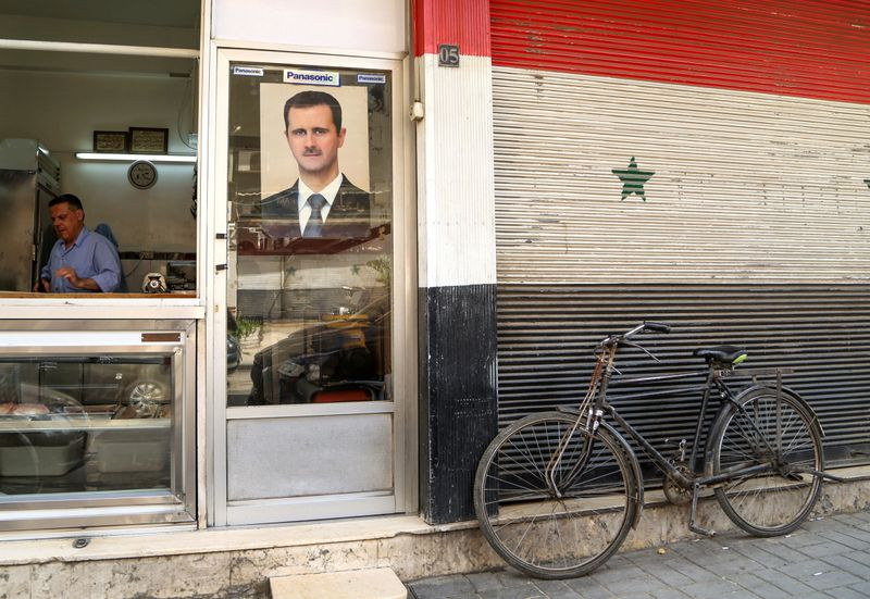 © Reuters. FILE PHOTO: A picture of Syrian President Bashar al-Assad is seen on a door of a butcher shop, during a lockdown to prevent the spread of the coronavirus disease (COVID-19), in Damascus
