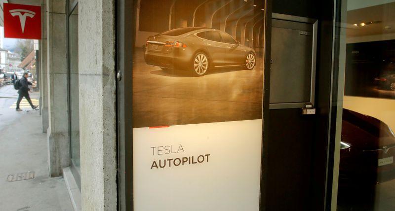 © Reuters. FILE PHOTO: Advertisement promotes Tesla Autopilot at a showroom of U.S. car manufacturer Tesla in Zurich