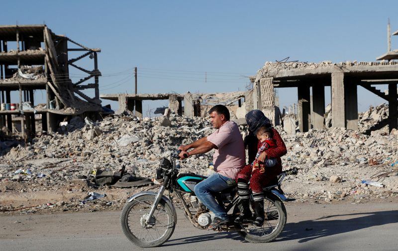 © Reuters. FILE PHOTO: Motorists ride a motorcycle past ruins of buildings destroyed during fightings with the Islamic State militants in Kobani