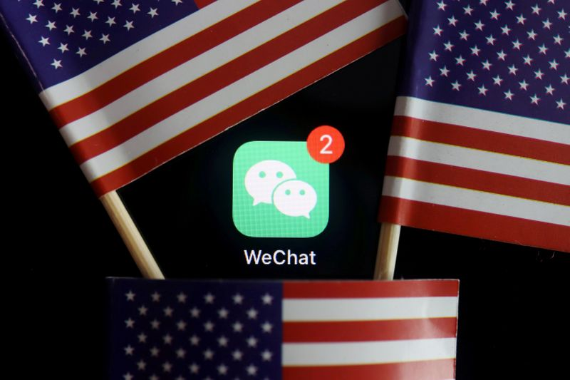 © Reuters. FILE PHOTO: The messenger app WeChat is seen among U.S. flags in this illustration picture
