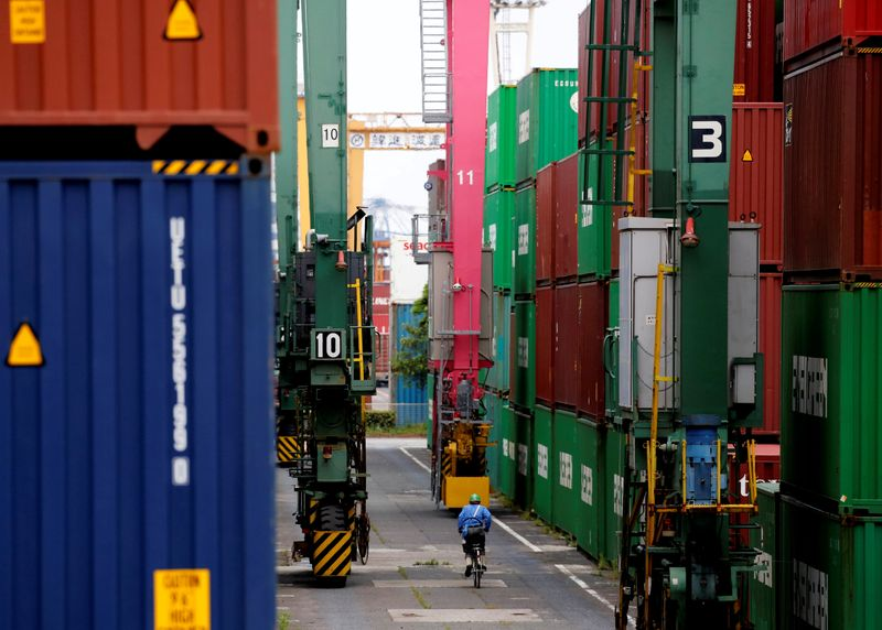 © Reuters. FILE PHOTO: A man on a bicycle rides past containers at an industrial port in Tokyo