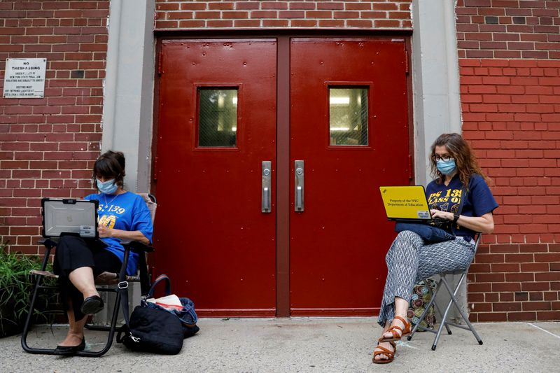 © Reuters. Teachers work outside their school building for safety reasons as they prepare for the delayed start of the school year in Brooklyn, New York