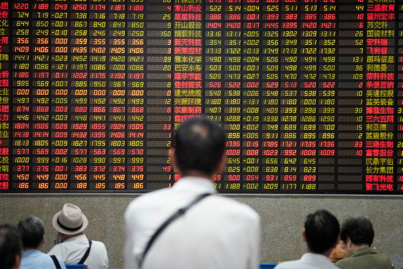 © Reuters. People look at an electronic board showing stock information at a brokerage house in Shanghai