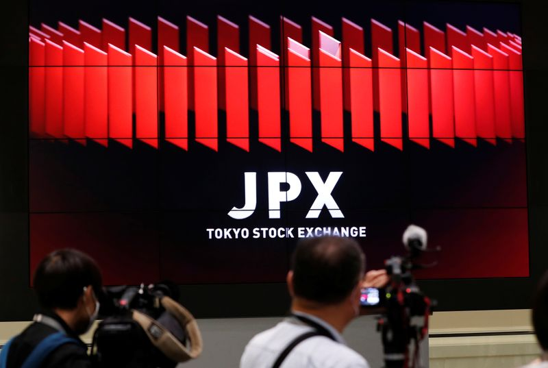 © Reuters. TV camera men wait for the opening of market in front of a large screen showing stock prices at the Tokyo Stock Exchange in Tokyo