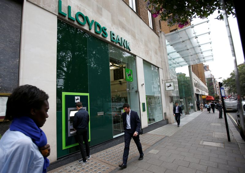 © Reuters. FILE PHOTO: People walk past a branch of Lloyds Bank at Berkeley Square in London