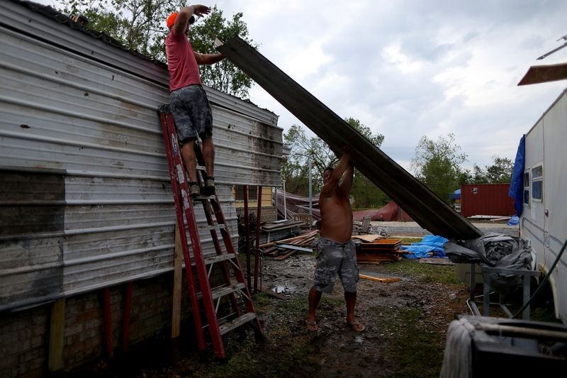 © Reuters. Jeremy Wood and Danny Schwem move a piece of metal roofing while making repairs as Hurricane Delta approaches in Lake Charles