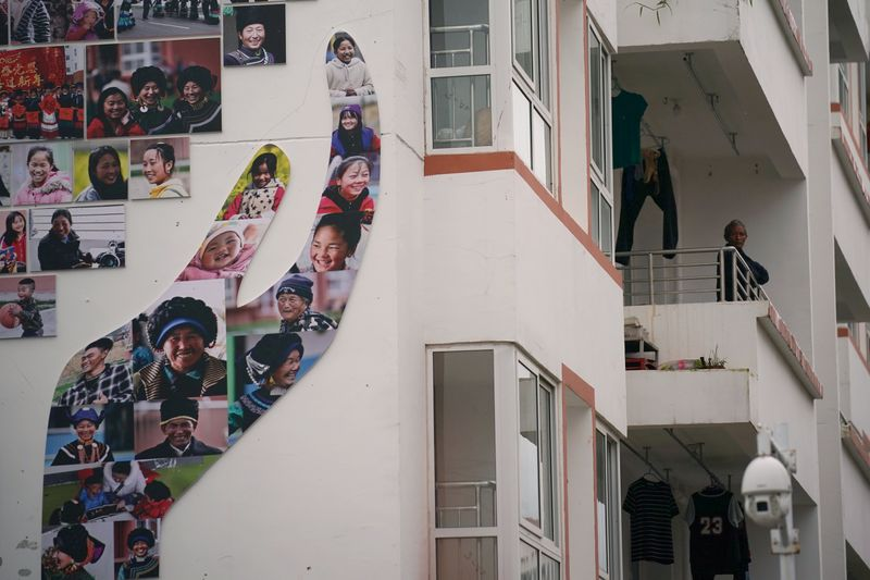 © Reuters. Man looks on at a balcony of a residential building at the Chengbei Ganen Community in Yuexi