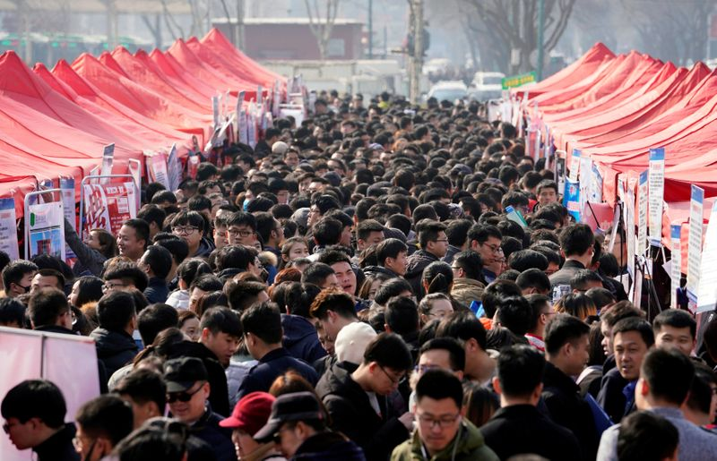 © Reuters. Job seekers crowd a job fair at Liberation Square in Shijiazhuang