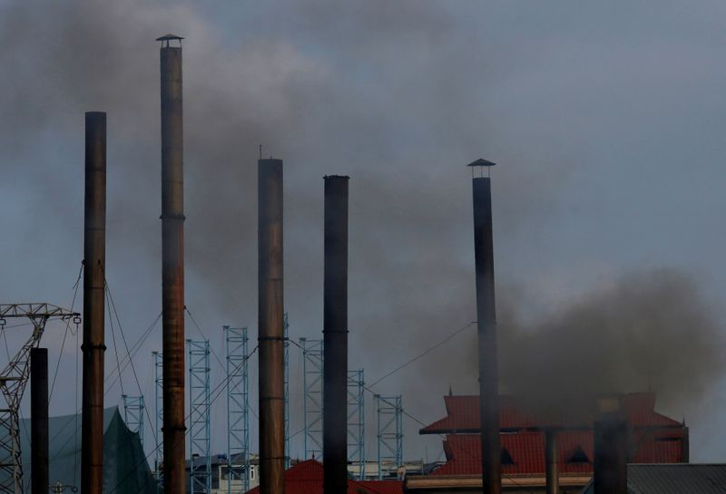 © Reuters. FILE PHOTO: Smoke rises from the chimney of a paper factory outside Hanoi