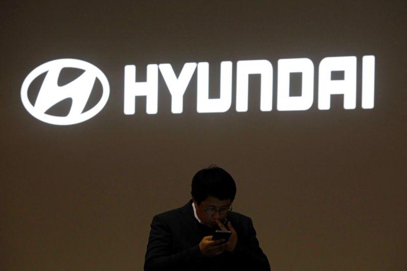 © Reuters. A man walks past the logo of Hyundai Motor during the 2019 Seoul Motor Show in Goyang