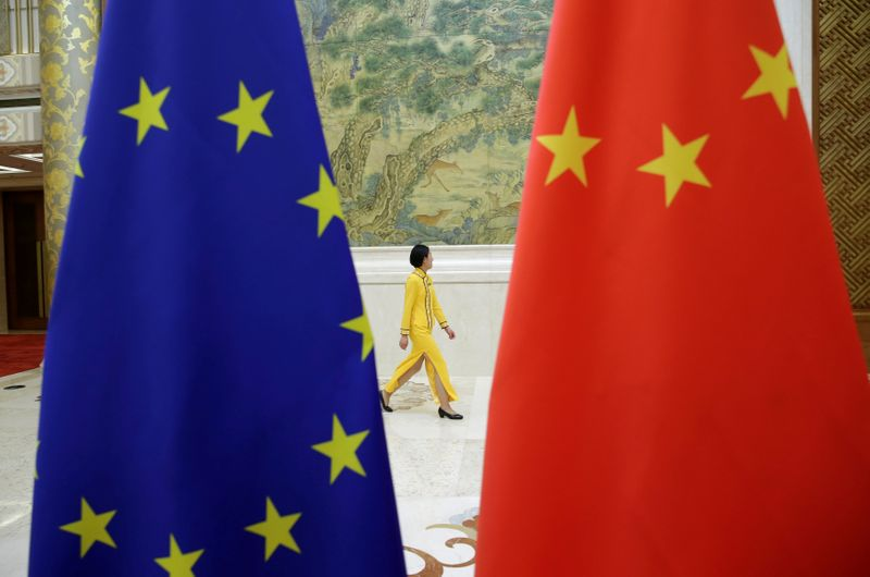 © Reuters. An attendant walks past flags of EU and China ahead of the EU-China High-level Economic Dialogue in Beijing