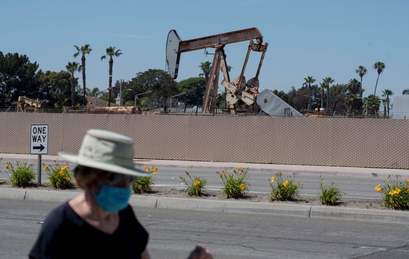© Reuters. A pedestrian wearing a protective mask walks past an oil derrick in Huntington Beach