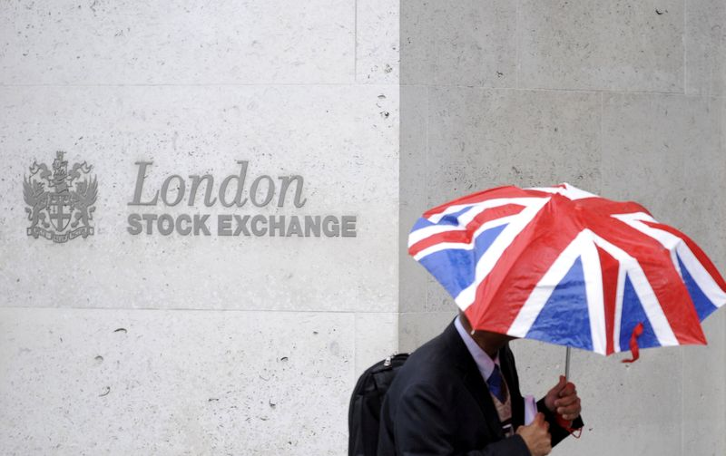 © Reuters. FILE PHOTO: A worker shelters from the rain as he passes the London Stock Exchange in the City of London