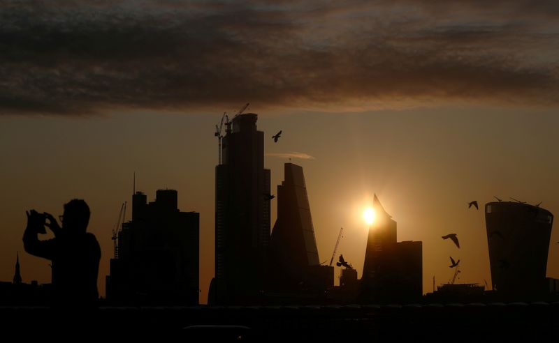 © Reuters. FILE PHOTO: A man takes a photograph of the skyline as the sun rises behind the city of London financial district in London