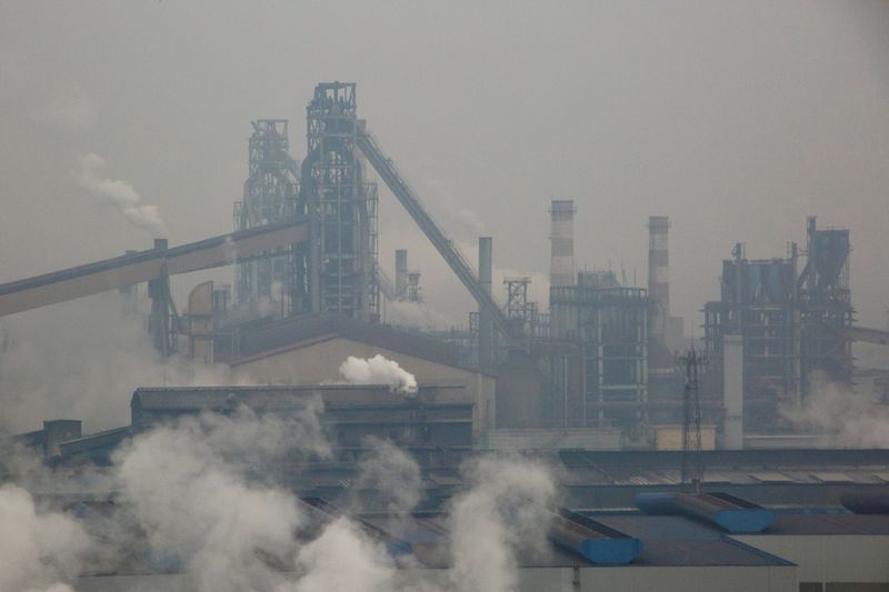 © Reuters. FILE PHOTO: Smoke and steam rise from a steel plant in Anyang