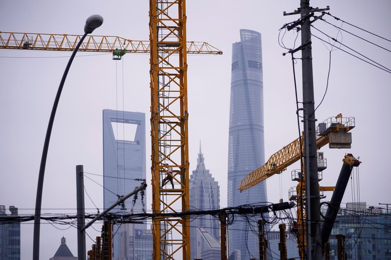 © Reuters. A worker is seen on a crane at a construction site in front of Lujiazui financial district, in Shanghai