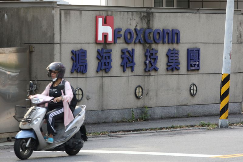 © Reuters. A person riding a scooter wears a mask amid the outbreak of the coronavirus disease (COVID-19), while passing a Foxconn office building in Taipei