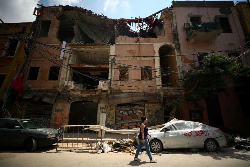 © Reuters.  FOTO DE ARCHIVO: Rita Faraj Oghlo, de 31 años, pasa frente a un edificio dañado en Beirut