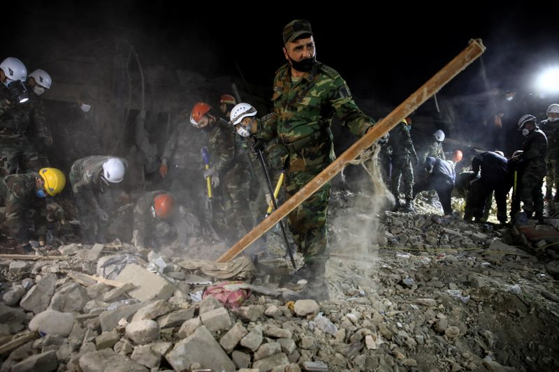 © Reuters. Search and rescue teams work on the blast site hit by a rocket in the city of Ganja