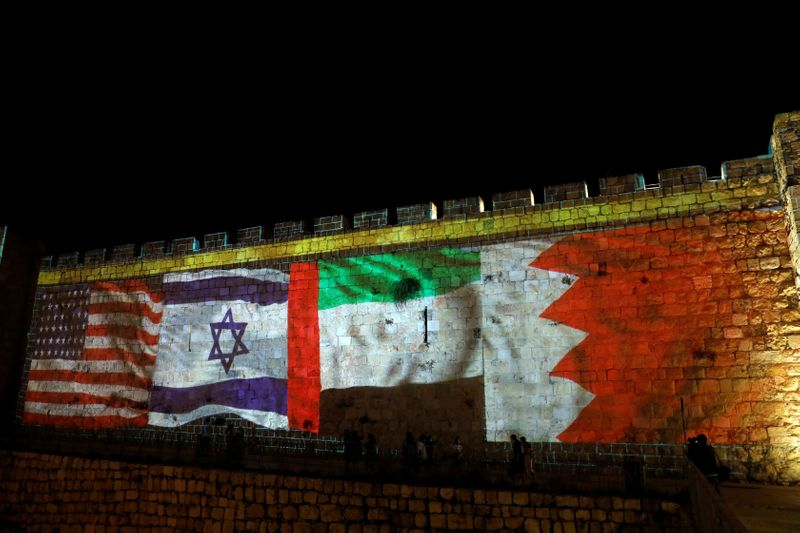 © Reuters. National flags of Bahrain, UAE, Israel and the U.S. are projected on the walls of Jerusalem's Old city