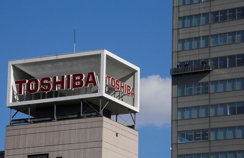 © Reuters. The logo of Toshiba Corp is seen as Window cleaners work on the company's headquarters in Tokyo