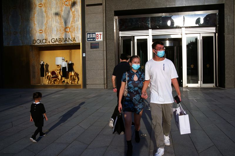 © Reuters. FILE PHOTO: People wearing face masks following the COVID-19 outbreak walk out of a shopping mall in Beijing