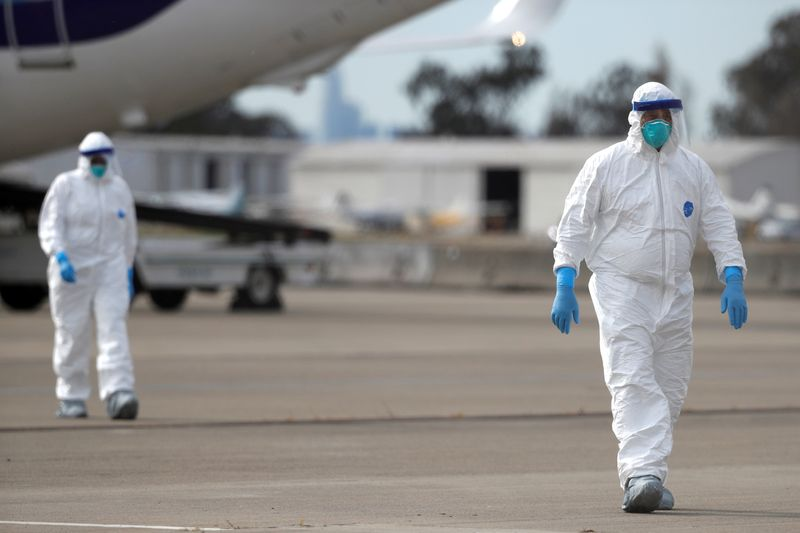 © Reuters. Workers in protective gear walk on the tarmac at Oakland International Airport as authorities continue debarkation from the ship after 21 people on board have tested positive for the COVID-19 coronavirus in Oakland