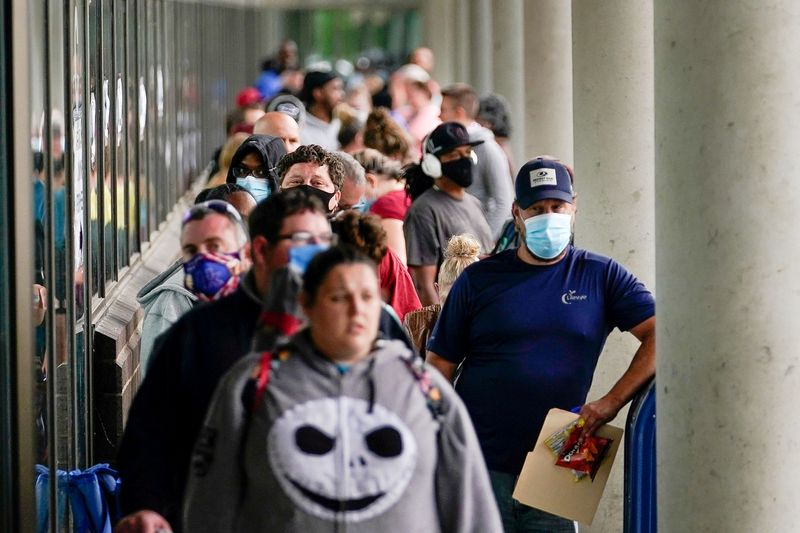 © Reuters. FILE PHOTO: Hundreds of people line up outside a Kentucky Career Center hoping to find assistance with their unemployment claim in Frankfort