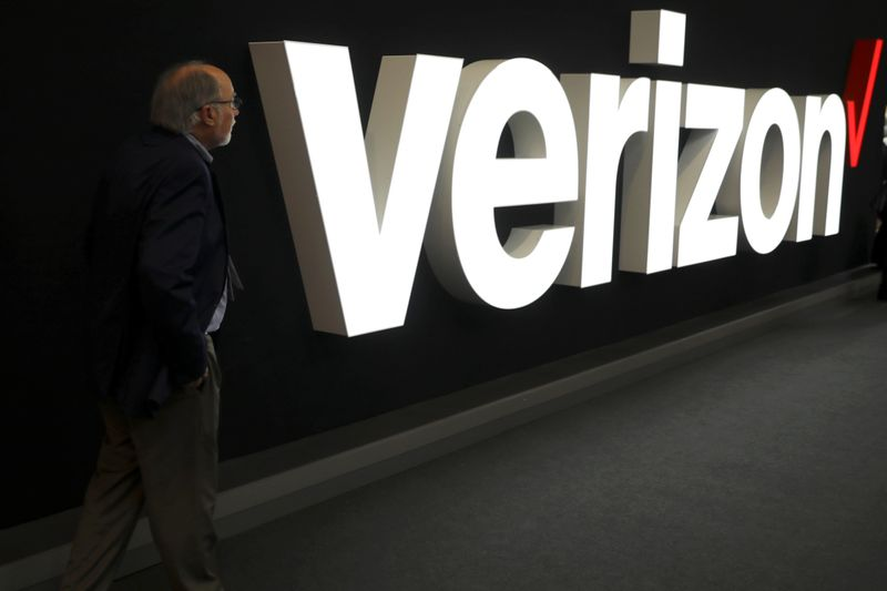 © Reuters. A man stands next to the logo of Verizon at the Mobile World Congress in Barcelona