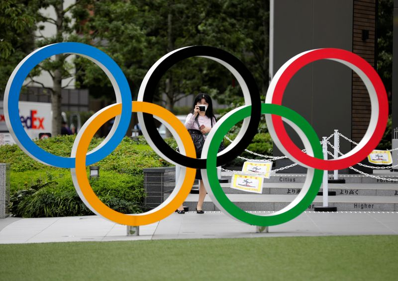 © Reuters. FILE PHOTO: A woman wearing a protective mask amid the coronavirus disease (COVID-19) outbreak, takes a picture of the Olympic rings in front of the National Stadium in Tokyo