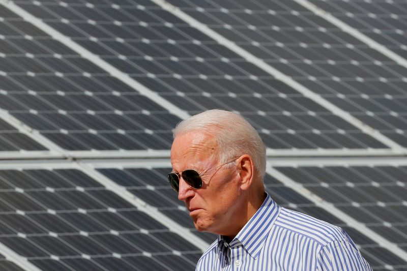 © Reuters. FILE PHOTO: Democratic 2020 U.S. presidential candidate Biden walks past solar panels in Plymouth