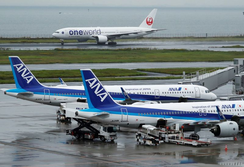 © Reuters. A Japan Airlines (JAL) aircraft takes off near All Nippon Airways (ANA) aircrafts, amid the coronavirus disease (COVID-19) outbreak at Haneda Airport in Tokyo