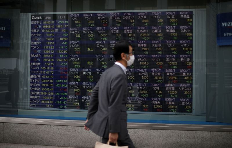 © Reuters. A man wearing protective face mask walks in front of a stock quotation board outside a brokerage in Tokyo